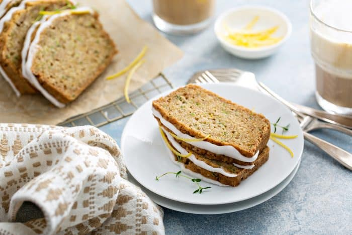 Two slices of lemon zucchini bread stacked on a white plate, with additional slices of the bread and a cup of iced coffee in the background