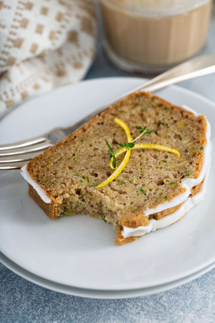 Slice of lemon zucchini bread with a bite taken out of the corner on a white plate next to a fork