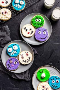 Halloween monster decorated sugar cookies arranged on three gray plates