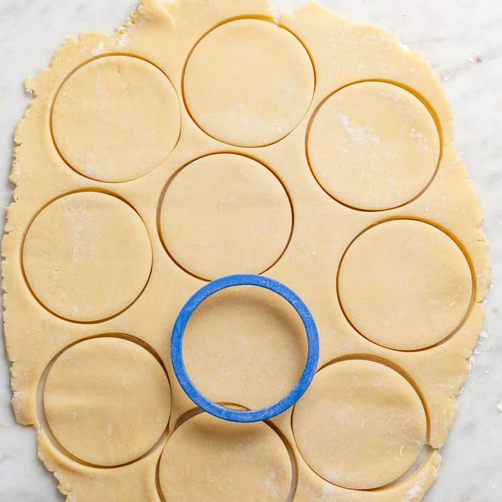 Circle cookie cutter cutting out circles of sugar cookie dough