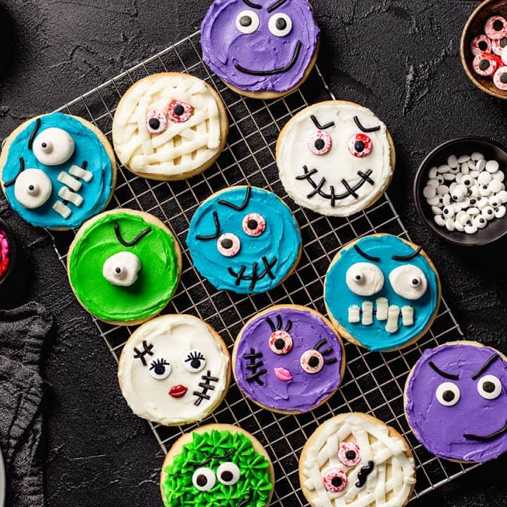 Sugar cookies decorated like halloween monsters on a wire rack