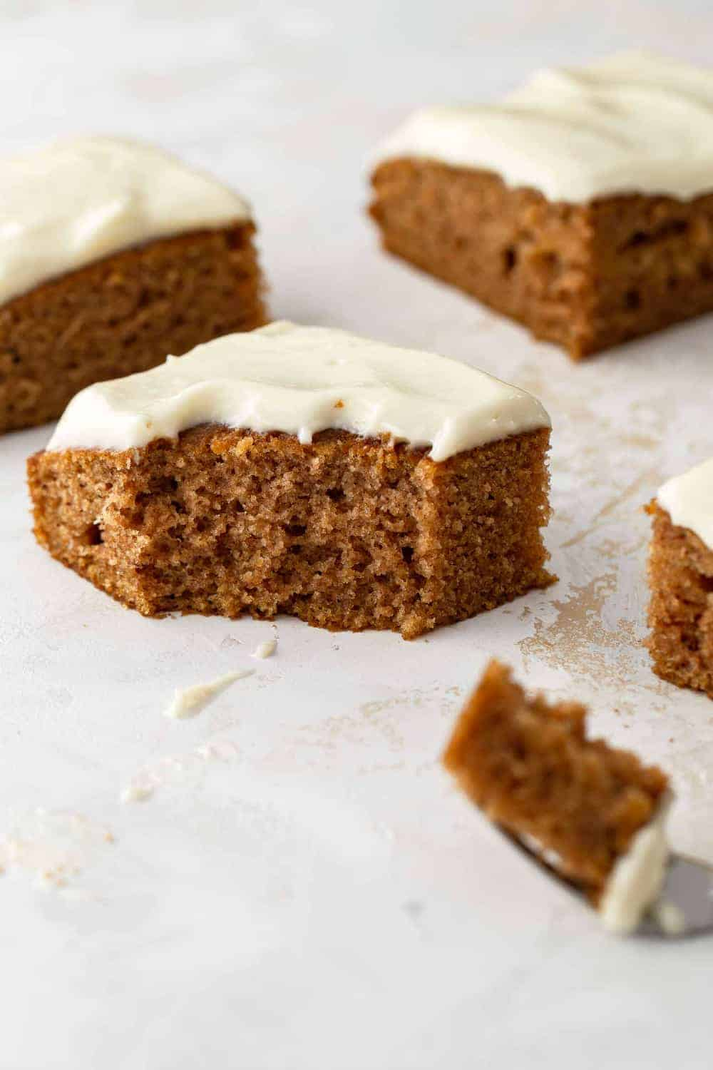 Side view of a pumpkin bar with cream cheese frosting with a bite taken out of it