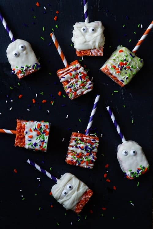 Marshmallow treats are given a Halloween twist and served on paper straws to create a sweet and festive dessert worthy of any Halloween celebration.