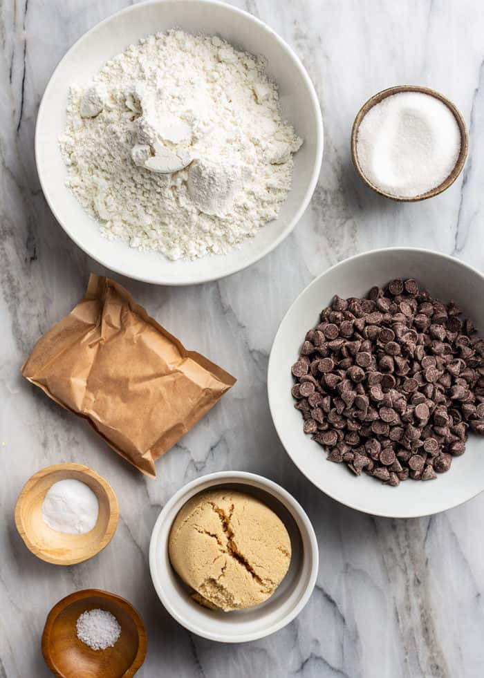 Ingredients for chocolate chip pudding cookies arranged on a marble countertop
