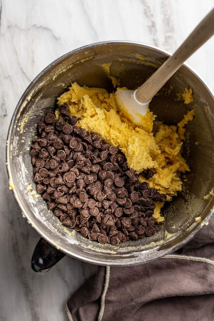Spatula folding chocolate chips into pudding cookie dough