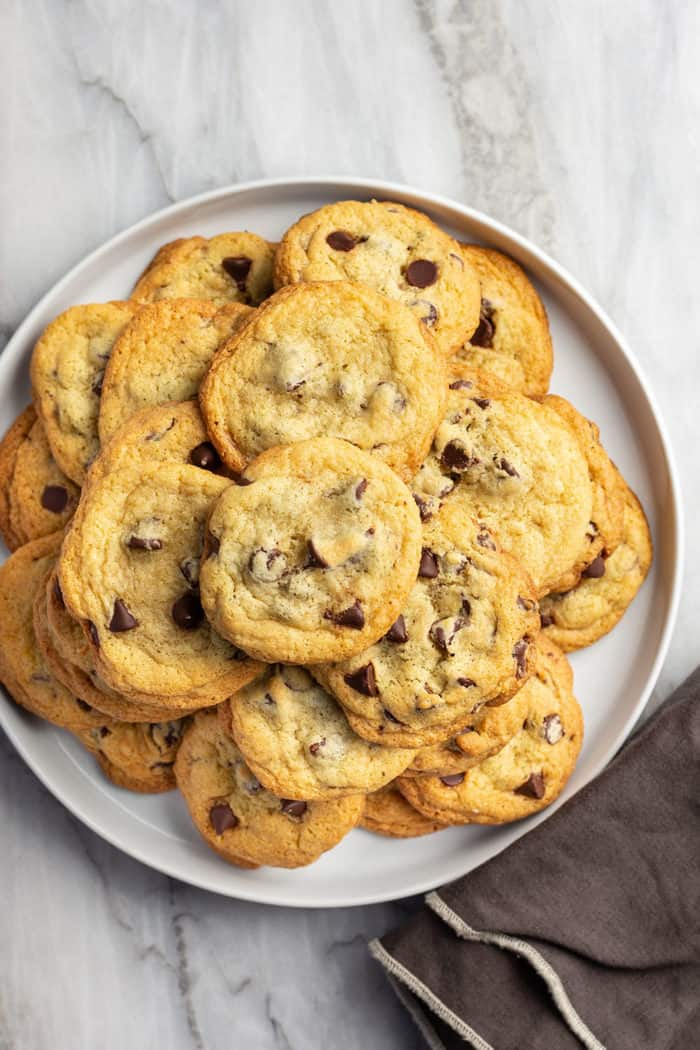 White platter filled with chocolate chip pudding cookies, set on a marble countertop