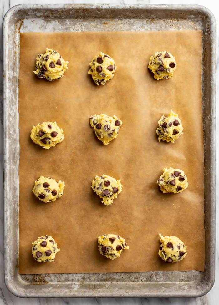 Portioned balls of chocolate chip pudding cookie dough on a parchment-lined baking sheet, ready to bake