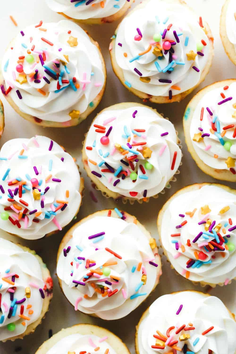 Overhead view of frosted funfetti cupcakes, topped with sprinkles