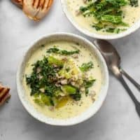Zuppa toscana in white bowls on a marble countertop next to spoons and bread