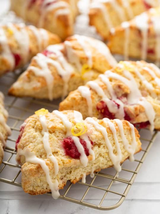 Close up of glazed lemon raspberry scones on a wire cooling rack
