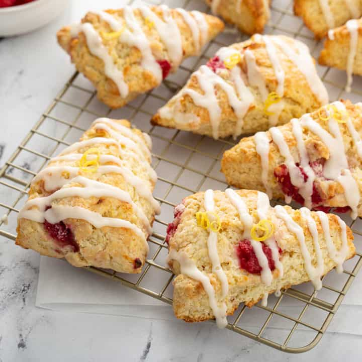 Lemon raspberry scones arranged on a wire cooling rack on a marble countertop