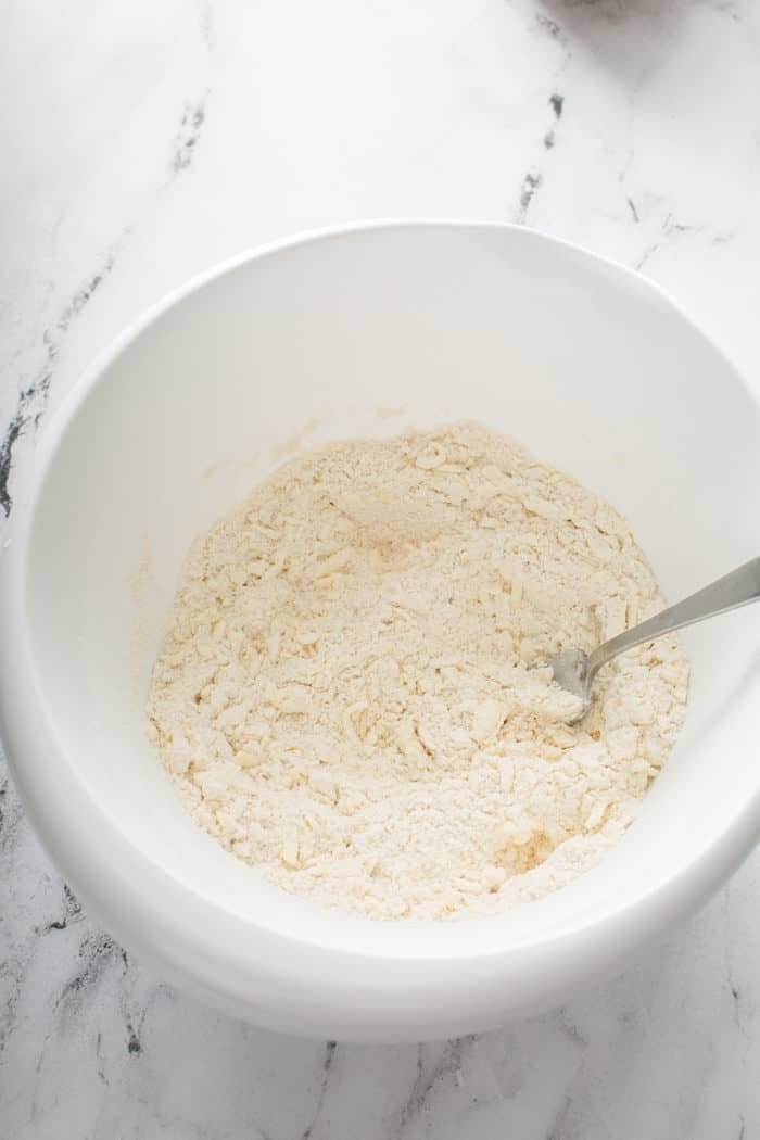 Crumbly butter and flour mixture for scones mixed together in a white mixing bowl
