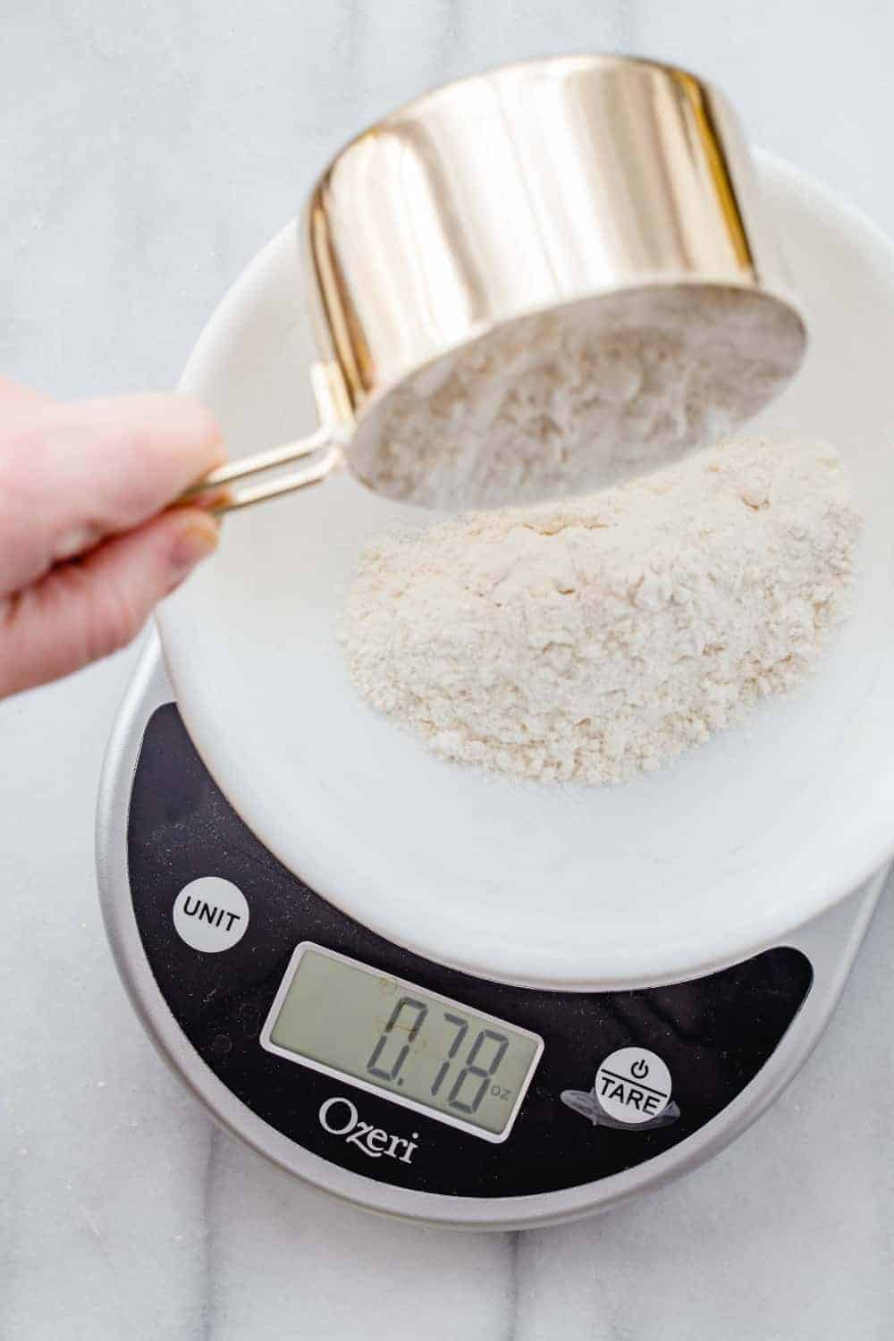 Hand pouring flour from a gold measuring cup into a white bowl on a digital scale