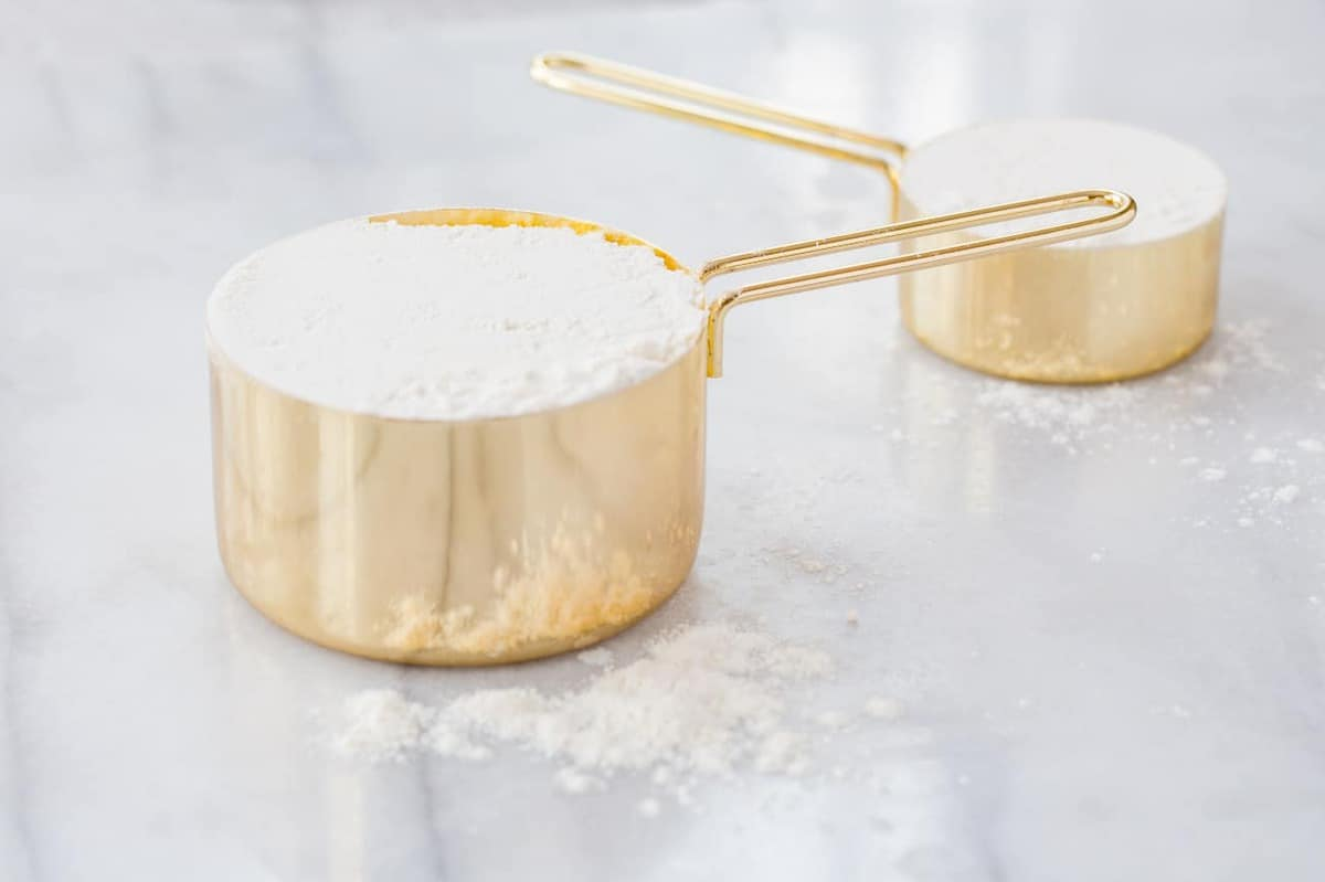 Two gold measuring cups filled with flour on a marble countertop