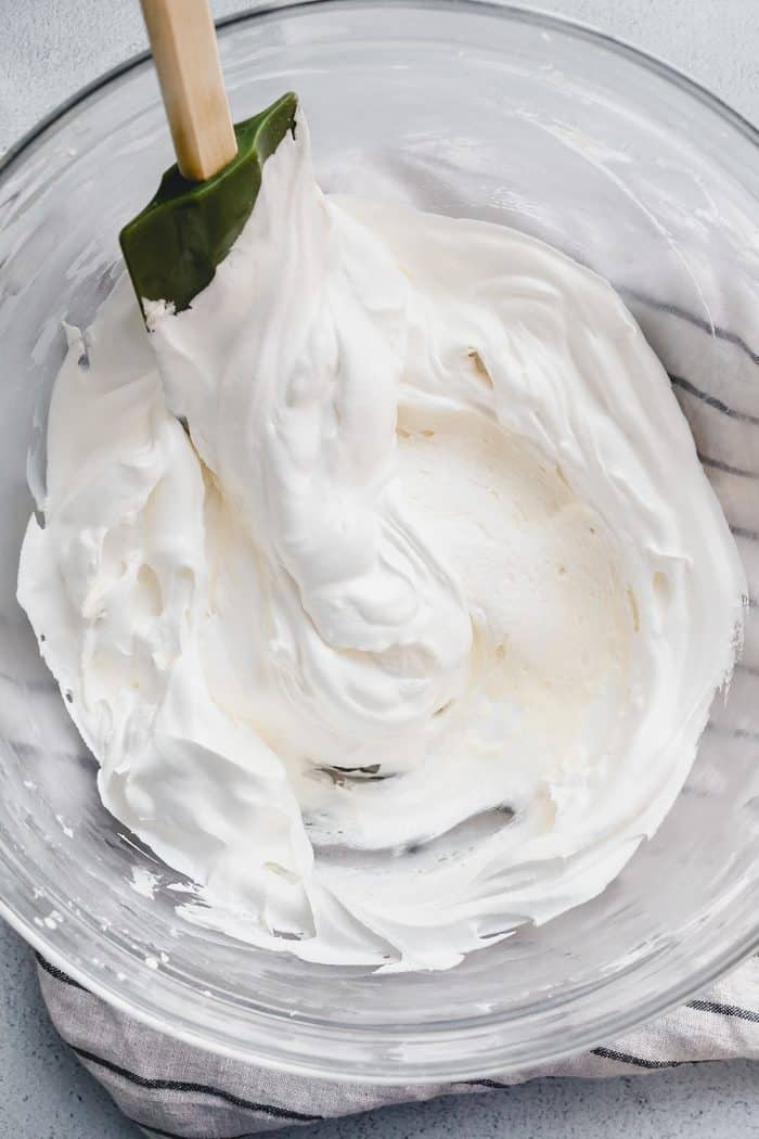 Spatula folding whipped topping into the filling for no bake oreo cheesecake in a glass mixing bowl