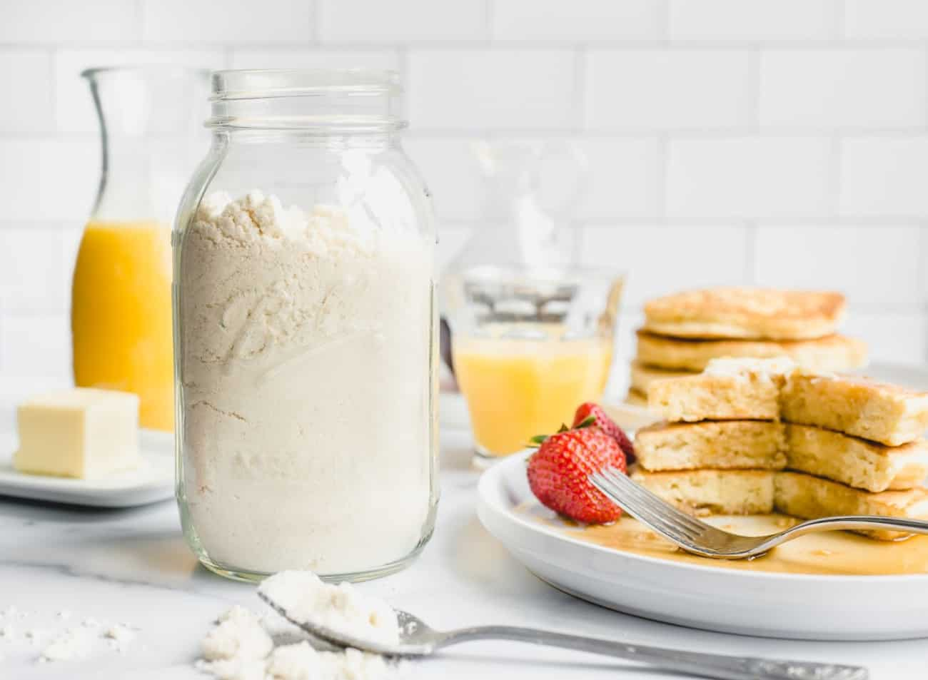 Jar full of homemade bisquick mix next to a stack of homemade pancakes