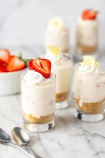 Shot glasses filled with creamy no-bake strawberry lemonade cheesecakes and topped with berries and lemons