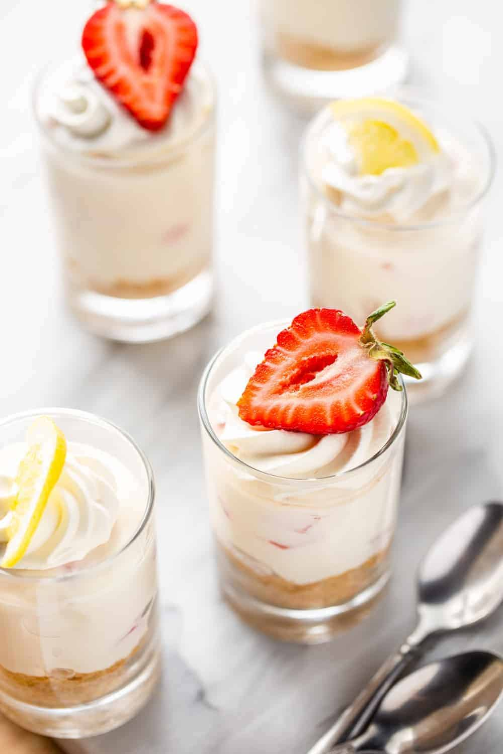 Mini no-bake strawberry lemonade cheesecakes in shot glasses, topped with whipped cream and a mixture of lemons and strawberries