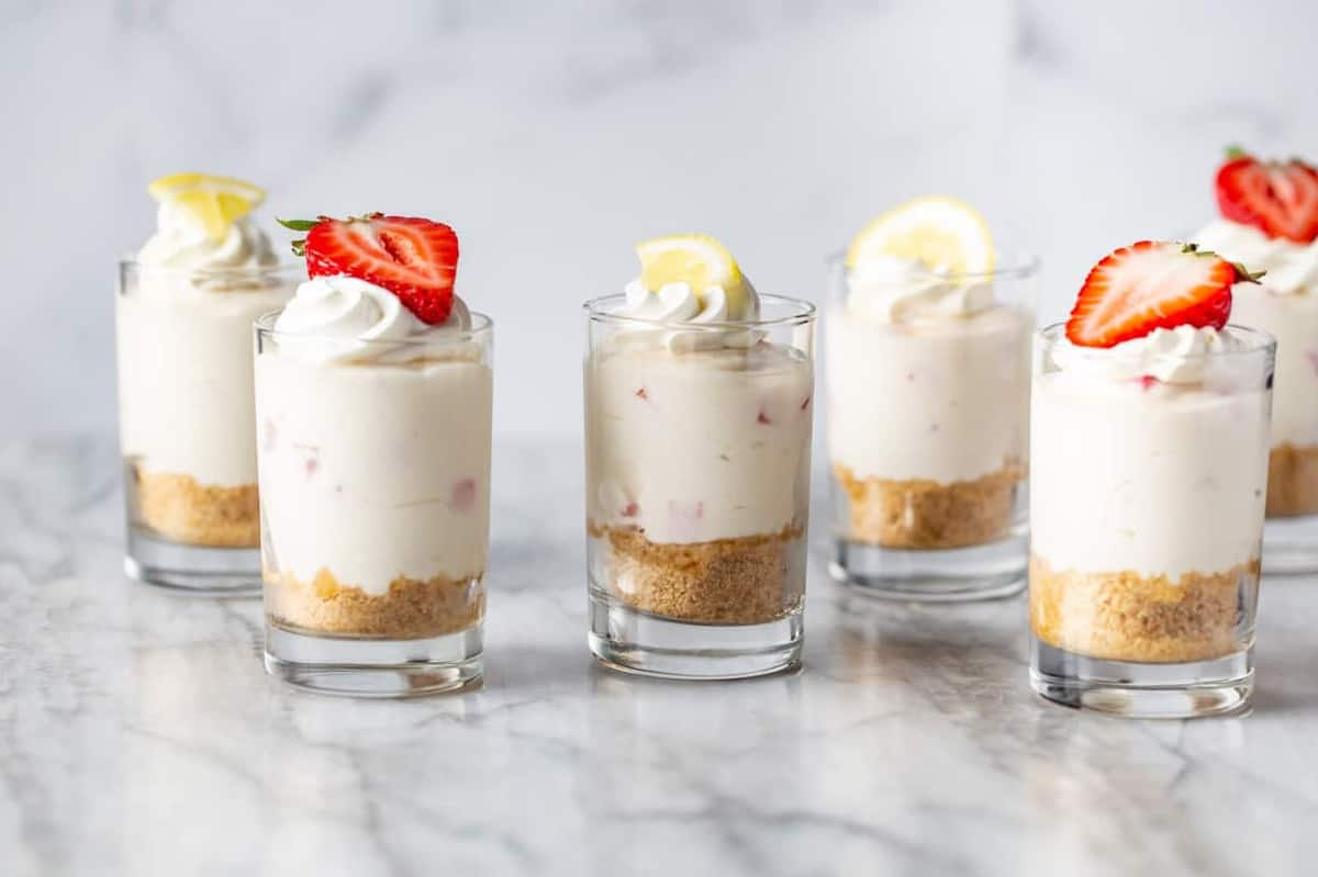 Dessert shot glasses filled with no-bake strawberry lemonade cheesecake arranged on a marble counter