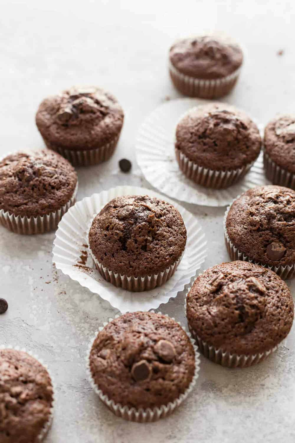 Baked chocolate zucchini muffins in white paper liners on a white surface
