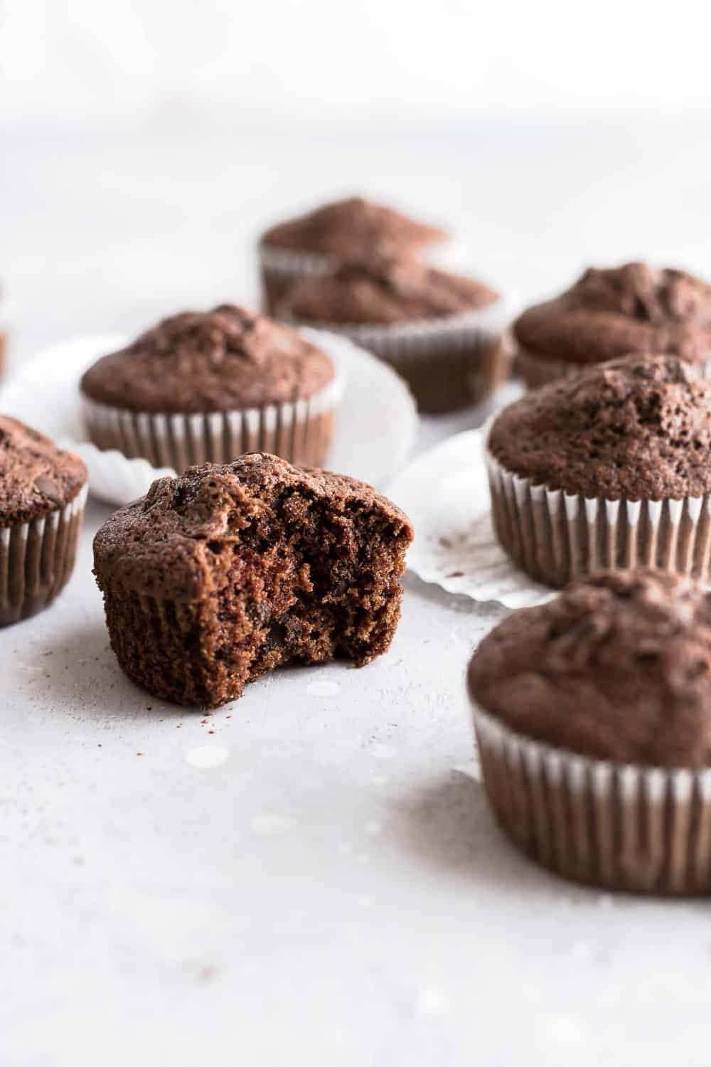 Side view of chocolate zucchini muffin with a bite taken out of it