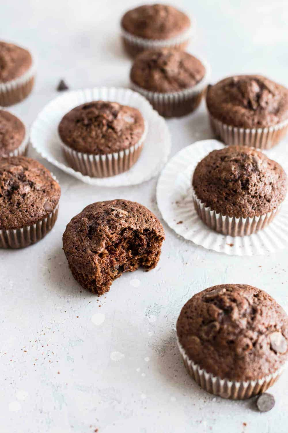 Half-eaten chocolate zucchini muffin surrounded by other chocolate muffins
