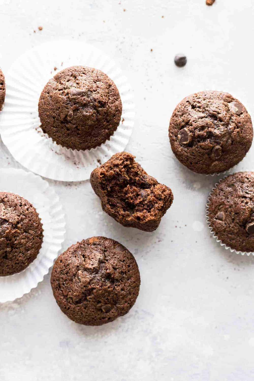 Baked chocolate zucchini muffins on a white surface