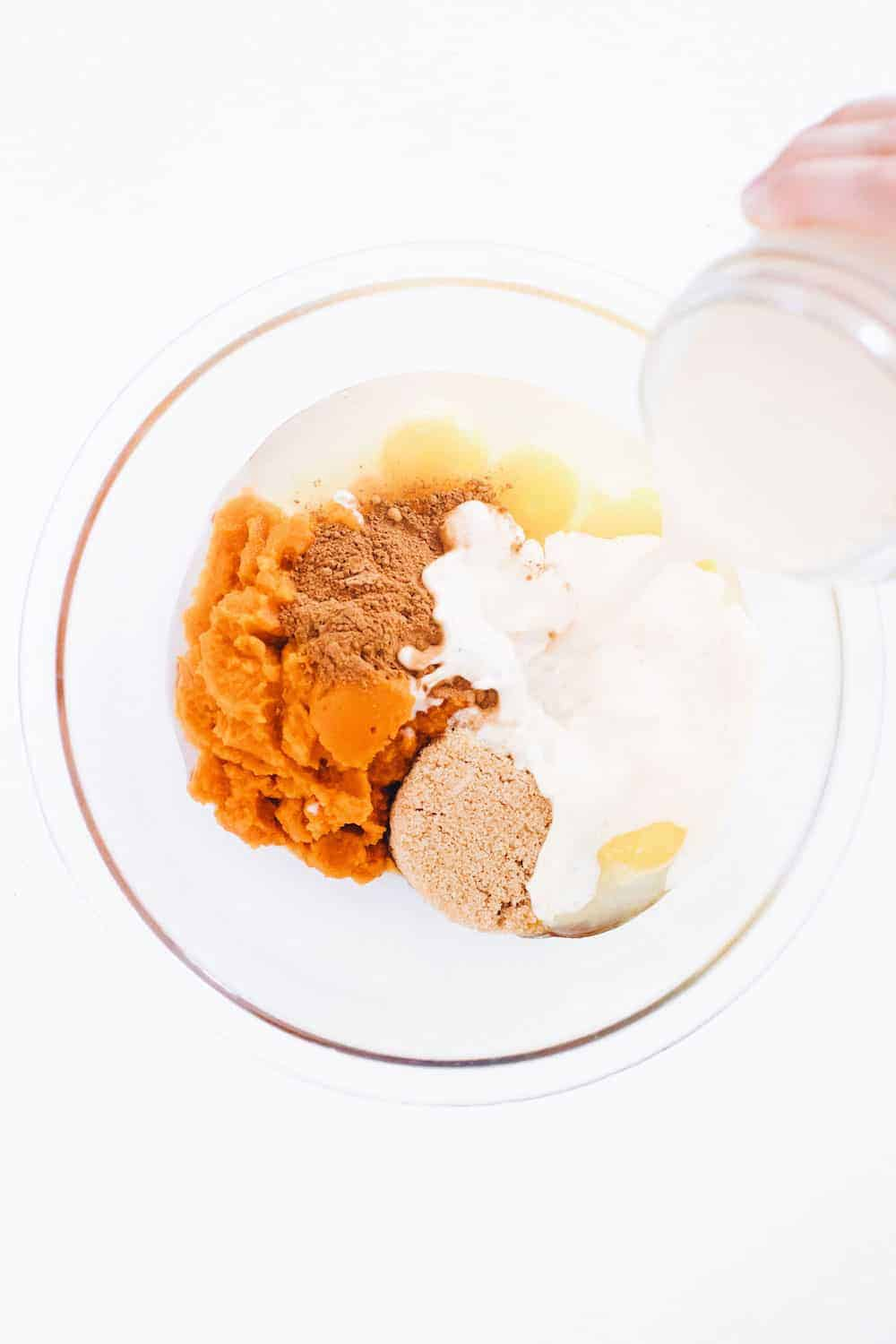 Pumpkin Crunch Cake ingredients in glass mixing bowl on counter