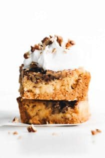 stacked pieces of pumpkin crunch cake with whipped cream and pecans