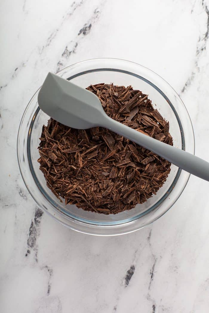Gray spatula set on the edge of a glass mixing bowl filled with chopped chocolate