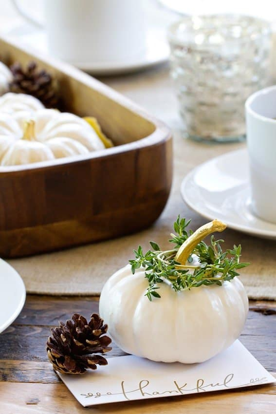 Painted White Mini Pumpkins make the perfect place setting for Thanksgiving.