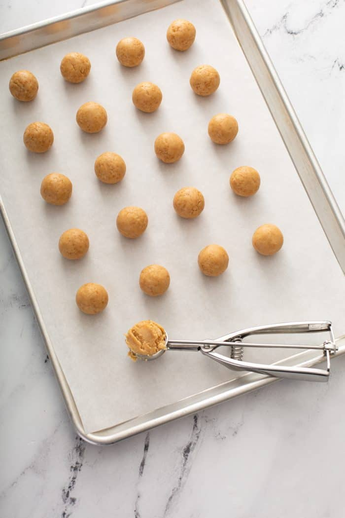 shaped cookie balls lined up on a parchment-lined baking sheet, ready to dip into chocolate