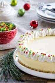 Sugar Cookie Cheesecake is baked up with a sugar cookie crust and topped with sweet vanilla whipped cream. So fun for the holidays!