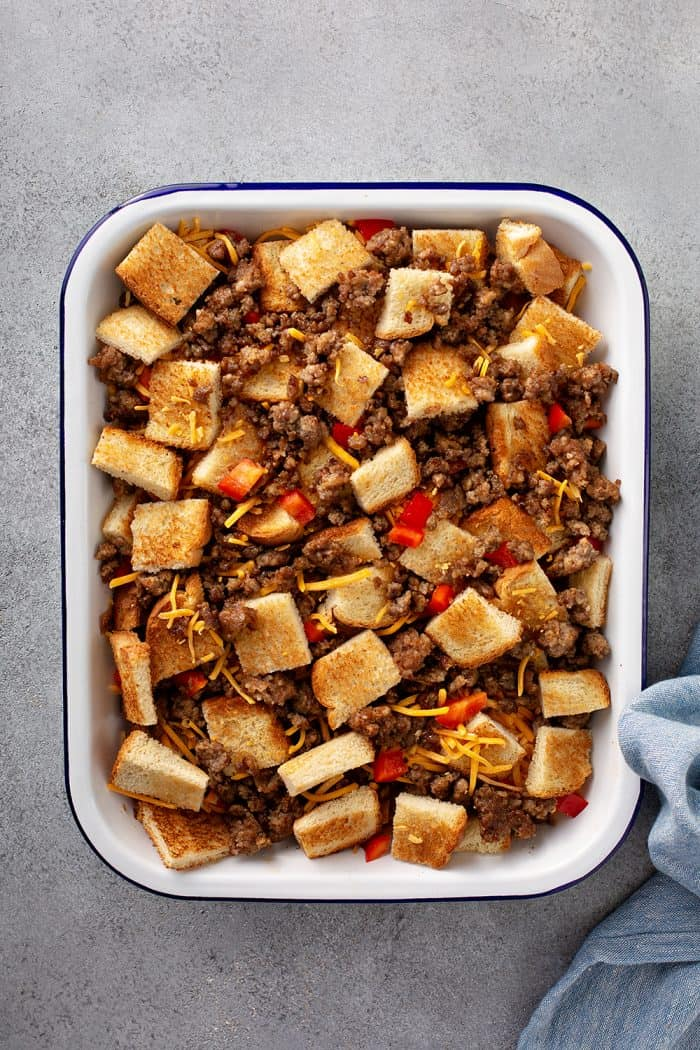 Overhead view of cubed bread, cooked sausage, and diced red pepper in a baking dish for breakfast casserole