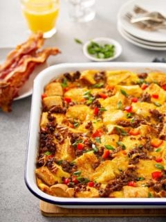 Casserole dish of make-ahead breakfast casserole on a gray counter with bacon and orange juice in the background