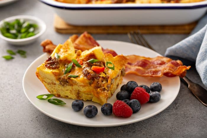 Side view of a slice of breakfast casserole next to bacon and fresh berries on a white plate with a casserole dish in the background