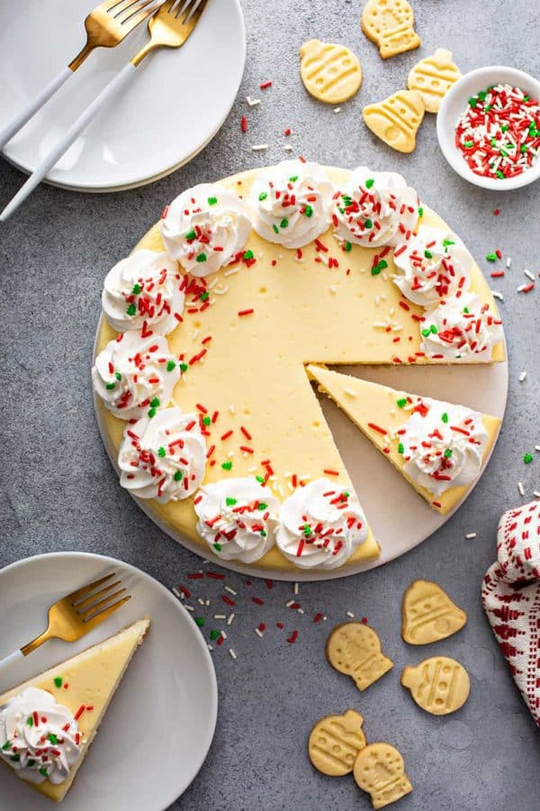 Overhead view of sliced sugar cookie cheesecake surrounded by white plates and sugar cookies