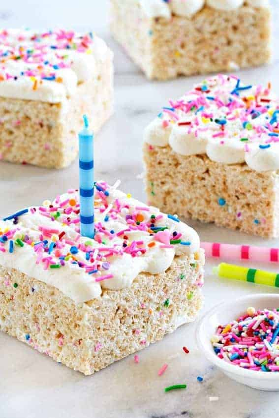 Birthday Marshmallow Cereal Treats are topped with buttercream frosting and loaded with sprinkles.