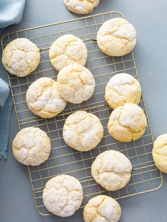 Gooey butter cookies scattered on a metal cooling rack on a gray counter
