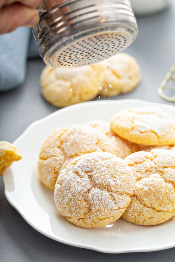 Powdered sugar being dusted on top of a pile of gooey butter cookies on a white plate
