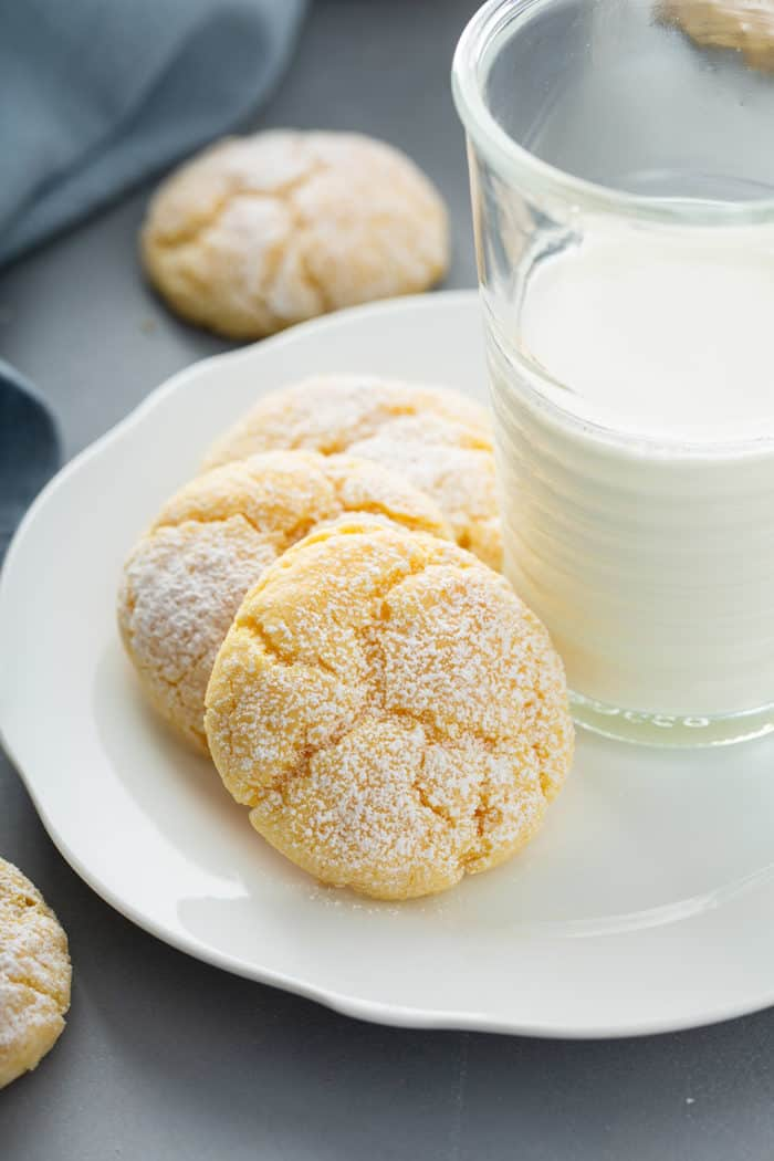Three gooey butter cookies arranged next to a glass of milk on a white plate
