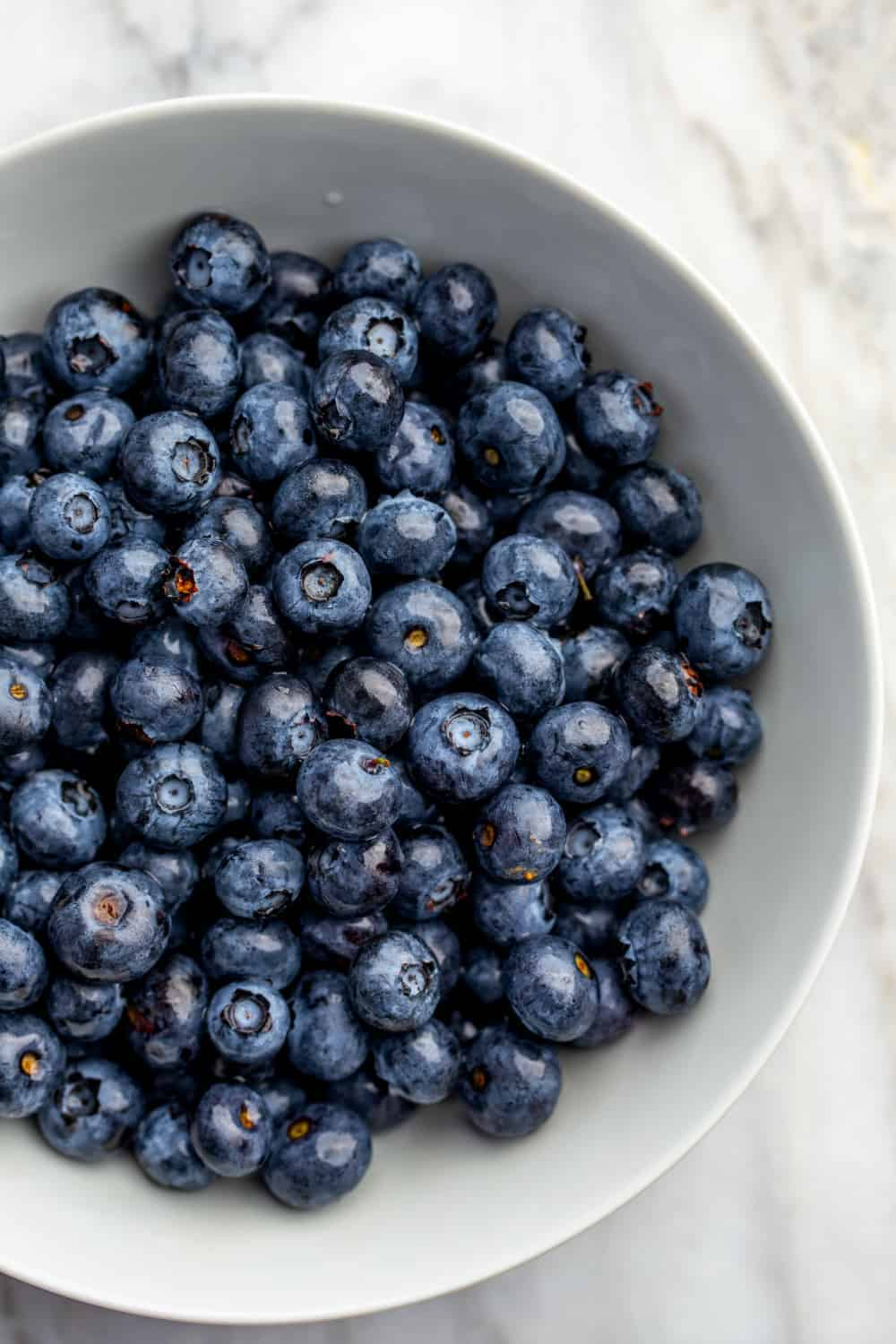 Fresh blueberries in a white bowl on a marble surface