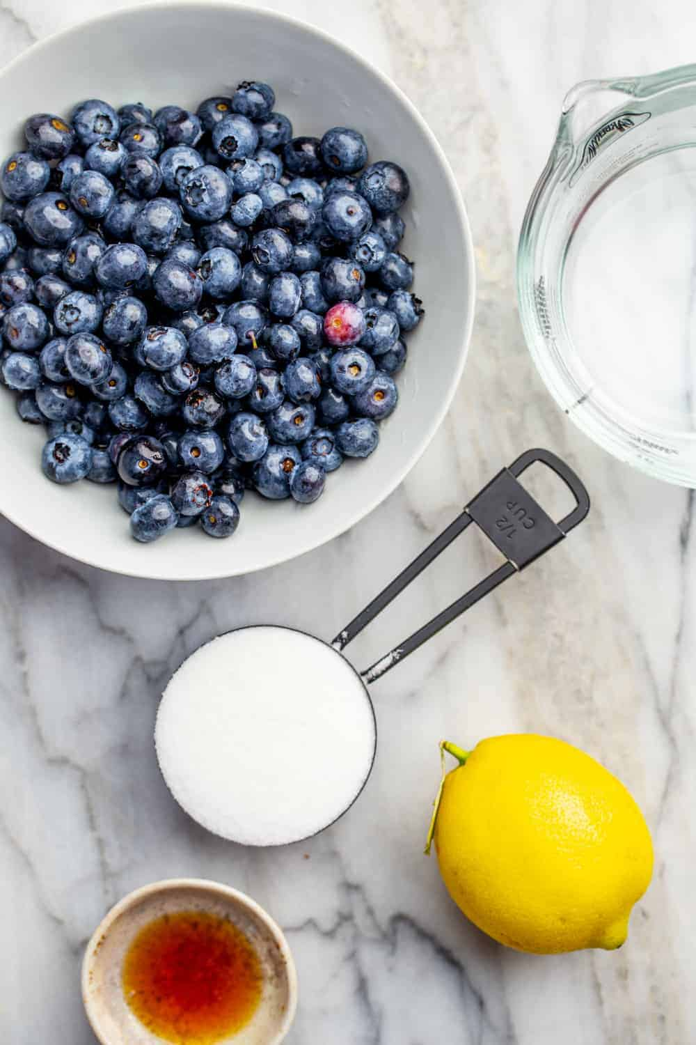 Ingredients for homemade blueberry sauce on a marble surface