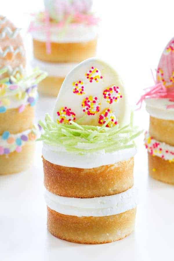 Mini Vanilla Bean Cakes are topped with edible Easter grass, pastel sprinkles, and an egg shaped marshmallow. So fun!