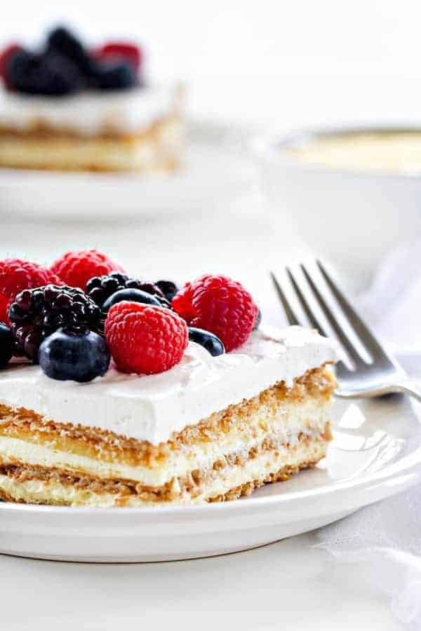 No Bake Layered Lemon Pie combines pudding, graham crackers, and lemon curd to create a delicious and bright spring dessert. Top each piece with fresh berries to make it even more amazing.