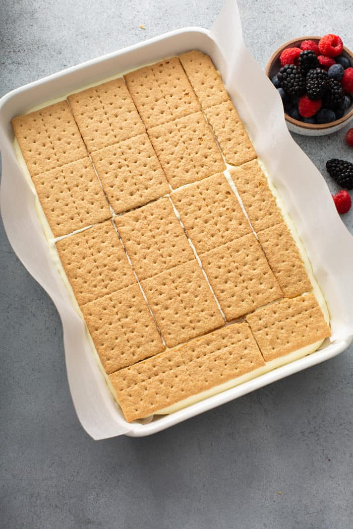 Layers of lemon icebox cake being assembled in a white baking dish