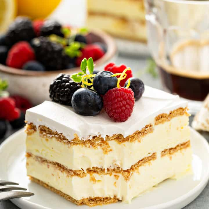 Slice of lemon icebox cake with a bite taken out of the corner, plated on a white plate and topped with fresh berries