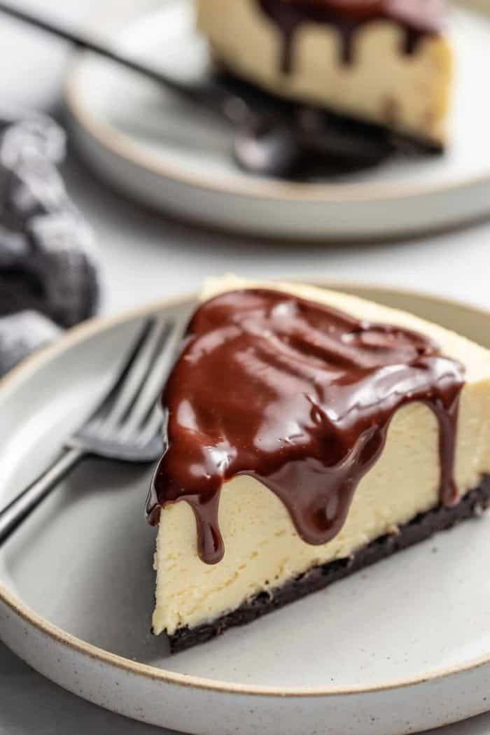 Slice of Baileys cheesecake next to a fork on a gray plate
