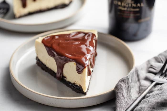 Slice of Baileys cheesecake topped with Baileys-spiked ganache on a gray plate