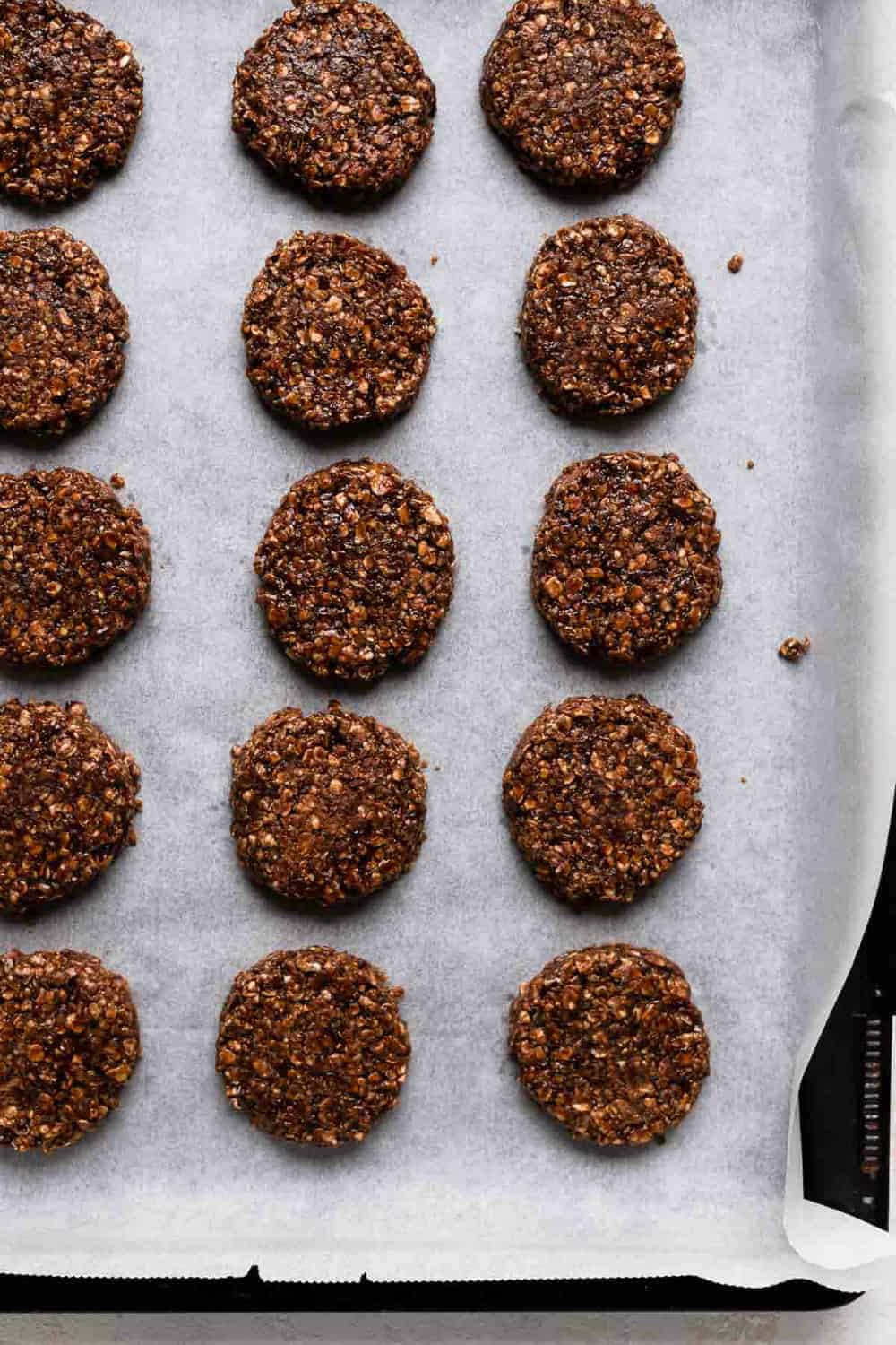 Flatted no bake cookies on a parchment-lined cookie sheet